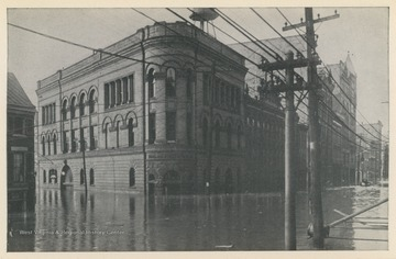 Photo postcard of a building located at the intersection of 16th Street and Main Street during a 1913 flood in Wheeling, W. Va. Postcard is part of a souvenir book of 1913 flood images.