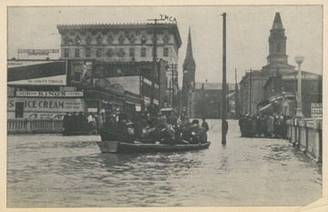 Photo postcard of a flooded street during a 1913 flood in Wheeling, W. Va.  At center, a group of people floats in a boat on the flooded street.  Several signs and buildings are visible in the background, one of which is identified as the Y.M.C.A.  Postcard is part of a souvenir book of 1913 flood images.