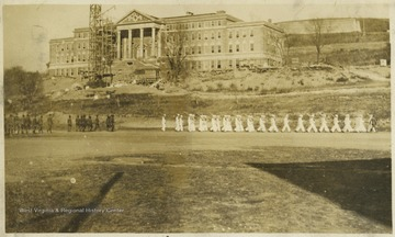 Navy ROTC members march down the field beneath the construction site of Stalnaker Hall.
