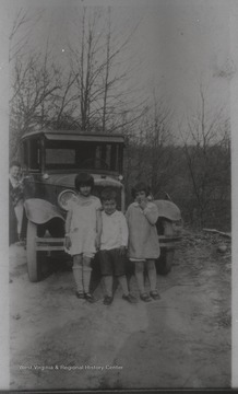 Edith Leontine Stephens (left), Gerald Otis Stephens (center), and neighbor girl Peggy Davis (right) stand beside an old-fashioned automobile. Edith and Gerald are the children of Eschol Lee and Essie Pearl Layfield Stephens. Eschol is the son of Leaman Clark Stephens, and the grandson of Stacy Stephens.