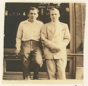 Two men sitting on a rail outside The Big 4 Drug Store, located on the corner of 3rd Avenue and Temple Street, in Hinton, W. Va.  A membership card identifies K. D. Foster, on the right, as the Vice President of The Rail Club.