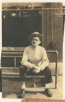 A man sitting on a rail outside The Big 4 Drug Store, located on the corner of 3rd Avenue and Temple Street, in Hinton, W. Va.  A membership card identifies B. O. Pettrie, Jr. as President of The Rail Club.