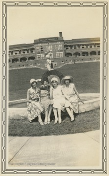 Four women sit on a fountain outside the Conely Hospital building at the Hopemont Sanitarium in August, 1930.