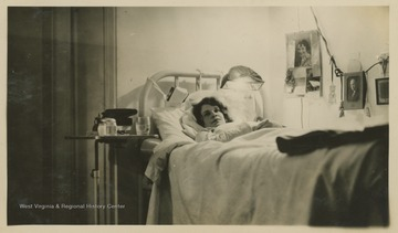 A woman reclines in a bed at Hopemont Sanitarium.  A light fixture is visible, attached to the head of the bed.  Another light fixture is seen plugged into the wall with several photos and items hung on the cord.