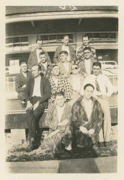 Thirteen men pose in front of a building in various states of dress.  Eleven are wearing bathrobes over lounge clothes, while the other two appear to be fully dressed.  Hospital beds are visible on a porch in the background.