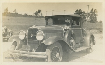 """Thrills! Front of Gore - Rather side. New 1930 Studebaker Coupe. Arthur Beaumont."" Woman in car is unidentified, but is likely Hester Luetta Harr."