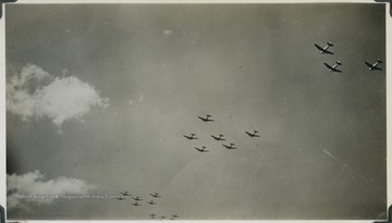 A fleet of U.S. bomber airplanes fly across the sky. The photograph comes from a U.S.S. West Virginia Scrapbook.