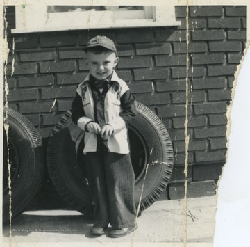 Butcher stands in front of a tire at Hitt's Filling Station in Weston, W. Va. He is 3 years old in this photograph.