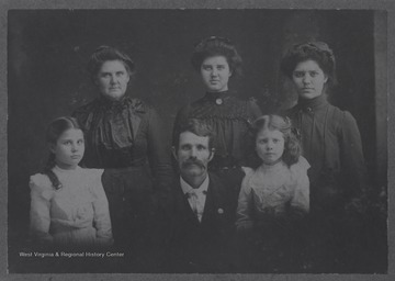 Group portrait of James W. Cooan (Koon) and his family.  Other family members in the portrait are likely his wife and four daughters or other female relatives.