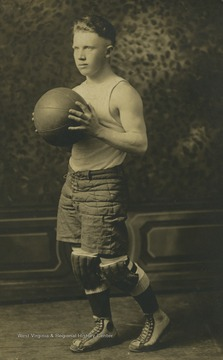 Photo postcard of John Edward Hallam. Hallam poses for a basketball photo at White School in Fairmont W. Va. He later married Stella Gattian.