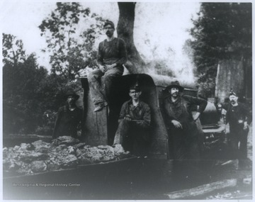 Five unidentified miners pose beside a truck loaded with coal.