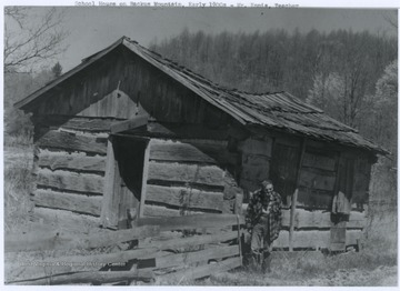 Mr. Ennis, the school teacher, stands outside of the old school building. The photograph was taken in the early 1900's.