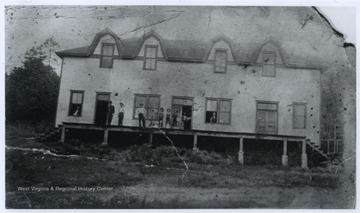 A group of men are pictured on the porch of the building. Subjects unidentified.