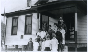 A group of school children pose outside of the school building with their teachers. Subjects unidentified.