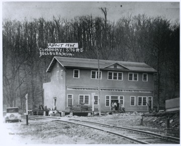 People are pictured at the store entrance. The building is situated beside railroad tracks.