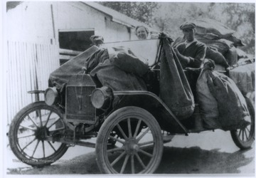 The older horse delivery method was replaced by this Ford automobile, driven by Mr. Thompson.