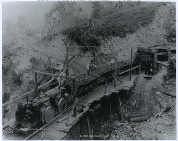 An electric haulage rail system at mine no. 2. An Africa-American miner is pictured in the conductor's seat on the train engine. Miners inspect the coal loaded into the carts before it is transported.