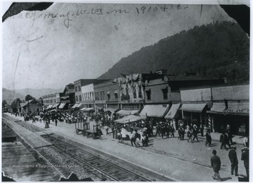 View of the town's main street which is situated next to railroad tracks.  The train station is visible at the far left, while businesses line the street.