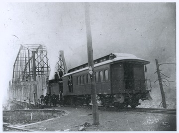 A group of men are pictured on and beside a train car.  A bridge in the background crosses the New River.