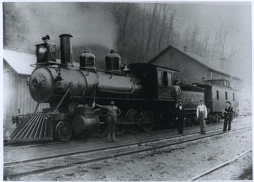 The engine used oil headlights. Five men are pictured on and beside the locomotive.
