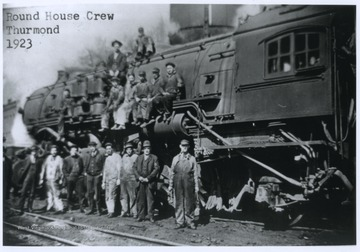 A group of men are pictured on and beside a locomotive. Subjects unidentified.