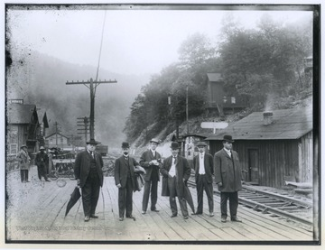From left to right are C. C. Beury, unidentified, C. L. Garvin, Sr., Paddy Ryan, unidentified, and unidentified. The men are coal operators and are posing on the south side of the train platform.