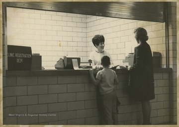 A mother and her child are greeted by a secretary at the WVU Medical Center.