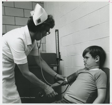 A nurse holds a stethoscope on a young boy's pulse.