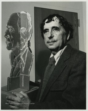 Famed Baltimore sculptor Kramer poses with a mock bust of a WVU faculty member identified as J. B. Rolunseir.