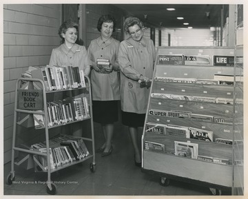 Three women collect books and magazines for patients at University Hospital.