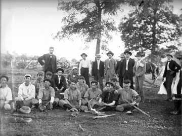 The players pose together for a team portrait. Two men in the background are sporting American flags on their jackets and hats, perhaps indicating it is Fourth of July.