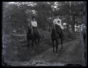 Two unidentified women riding sidesaddle along a dirt road.