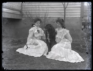 Two unidentified women sit with their pet dog on a lawn.
