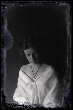 Portrait of an unidentified woman. She is wearing a necklace with a large pendant.