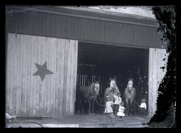 Four small children lead three horses out of the large, wooden stable.