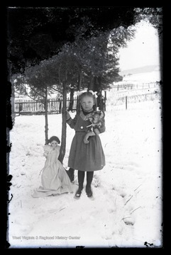 A young girl poses with her dolls outside in the snow.