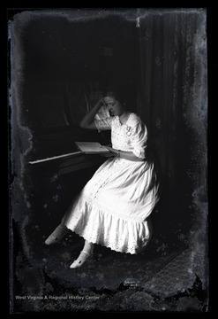 A young, unidentified girl leans against a piano as she reads a book.