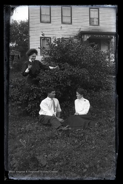 The woman dressed in black appears to be spying on the man and woman sitting beneath a bush.