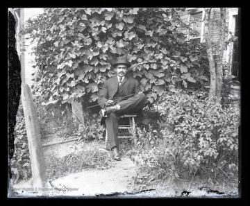 An African-American man sits with his legs crossed on a chair in a home garden. Subject unidentified.