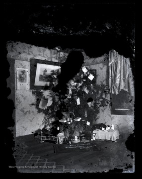 "A decorated Christmas tree stands in the corner of the house with presents sorted beneath it.  The home likely belongs to Orvis Zacheus ""Oz"" Gibson, a brother of the photographer, Scott Gibson."