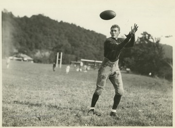 Glenn prepares to catch a football during football practice.