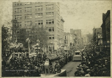 A crowd lines each side of High Street as parade floats travel down the street at 10 a.m.  The first float visible is shaped like a clothes iron.