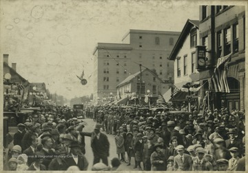Crowds fill the streets of Morgantown, W. Va. anticipating the parade. In the background is a Union Bank, right, and the building that is now Hotel Morgan, center.