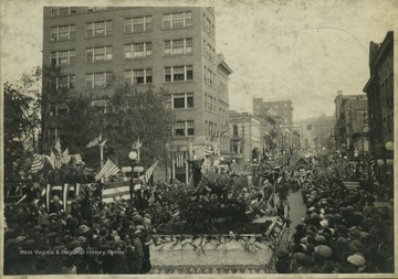 A crowd watches from the street as parade floats make their way down High Street. On the right, in front of the courthouse, is likely the grandstand.