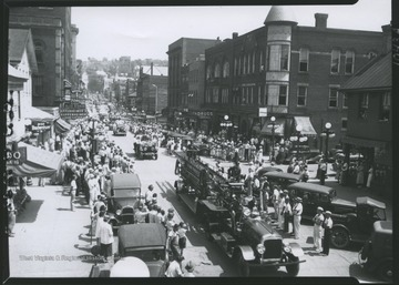 Crowds watch from either side of High Street as parade floats and a fire truck make their way down the street. In the background, various businesses are pictured, including Rogers Pharmacy, McVickers Pharmacy, Oppenheimer's Kuppenheimer, and The Sports Emporium.