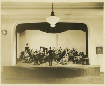 The man standing in the middle of the stage directs the musical group which consists of brass, string, woodwind, and percussion musicians inside the Women's Christian Temperance Union Community Building.