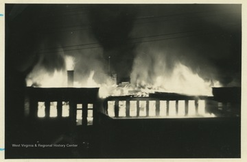Photograph shows the third floor fully engulfed in flames while the auditorium below has yet to catch fire.
