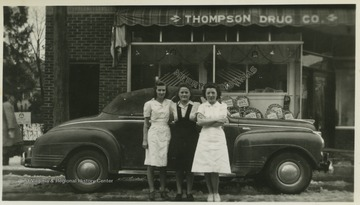 Three unidentified women pose beside a car parked in front of Thompson Drug Company.