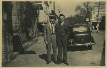 Hardman, left, and Hathaway, right, pose together by the street. In the background is Thompson Drug Co.