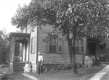 A man stands in a yard beside a house while a woman and child sit on the porch steps. Subjects unidentified.